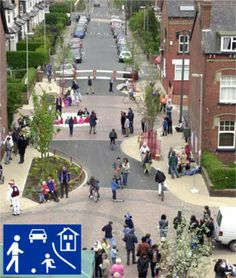 Woonerf street in the UK, designed with narrow roadway, curves, trees, removable bollards, and physical barriers improve safety for pedestri...