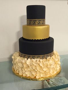 Black, gold, and ivory wedding cake with ruffled base and gold lace.