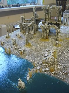 When I last showed the board, it had just been covered with sand, the buildings had been glued into place, everything was ready to paint. U...