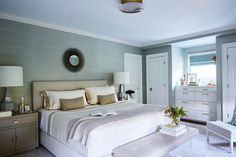 A Wolf-Gordon wallcovering sets a textured backdrop for the calming master bedroom. The bed itself is custom, upholstered with a Holly Hunt fabric, and the bedding is from Signoria Firenze. Over the bed, a dark, vintage sunburst mirror creates contrast against the light colors of the space. Two lamps from Visual Comfort are positioned on top of the custom nightstands. #masterbedroom #beachinspired #bluebedroom