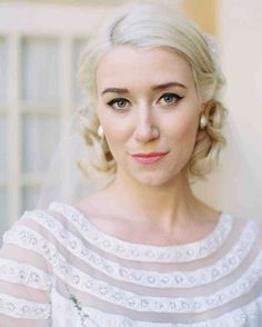 The Best Hairstyles for Every Wedding Dress Neckline | Martha Stewart Weddings - If your scoop-neck wedding dress errs on the vintage side, a curly faux-bob—and a bold cat-eye—is an on-theme choice. #weddinghair #weddinginspiration #hairstyle #wedding #weddinghairdo