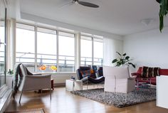 Surrounded by large windows, the living room is light and bright. The glass door on the left opens up to the main balcony.