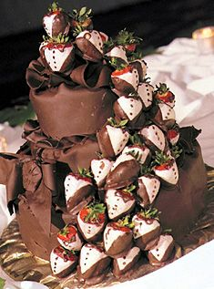 Chocolate Berries - This rich three-tiered thickly covered cake is topped with a chocolate cascade of white-chocolate and dark-chocolate-dipped strawberries.