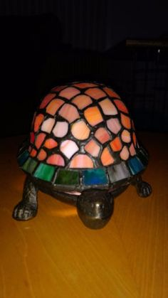 beautiful stained glass turtle shell lamp. feet, tail and head form the base and are made of metal. beautiful box turtles stained glass shell sits on the base. the base houses the light bulb etc. toggle switch on/off on electric cord. one glass piece on the side is cracked glass. some, what appears to be black paint, has rubbed off the soldering (a bit) in 2 spots. easy fix. i
