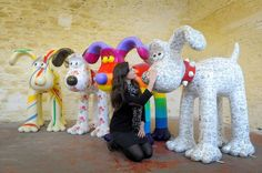 Lauren Vincent, fundraising manager for Gromit Unleashed, poses on April 19, 2013 with four, of around 70, Gromit sculptures painted by (left to right) Sir Paul Smith, Cath Kidston, Richard Williams and Simon Tofield, at a secret location in Bristol before they are placed for public view on an arts trail around the city from July 1st.