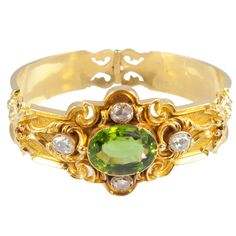 Unique Victorian Diamond, Peridot Gold Bracelet. The back of the bracelet is done in repousse with graduated size flowers on bloomed gold. The top of the bracelet centers 1 large faceted peridot surrounded by 4 rose-cut diamonds. Peridot: 20.30 carats, diamonds: 1.77 carats. Circa 1880