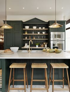 Gorgeous dark green kitchen cabinets accented with brass pendant lights, wood counter stools, a marble counter and a brass sink faucet. Dark Green Kitchen, Green Kitchen Cabinets, New Kitchen, Kitchen Dining, Kitchen Decor, Dark Cabinets, Kitchen Ideas, Country Kitchen, Brass Kitchen