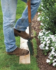 Here's an easy way to edge your lawn. Lay down a board, secure it with your foot, and drive a flat spade along one side. Move the board as you work your way down the bed.