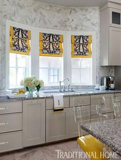 Kitchen. Carrara marble used as backsplash and on the walls above the range and windows.  Interesting use of subway tiles. Traditional Home