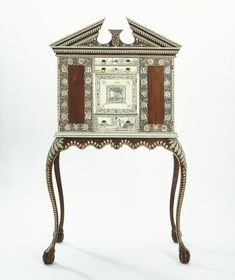 Cabinet and stand (Cabinet and stand) | V&A Search the Collections. This cabinet on stand is inspired by English models made in 1725-1750. It was made at Vizagapatam, a port on the east coast of India famous for its fine cabinet work. The maker has decorated the face of the cabinet with a combination of ivory inlay and ivory veneer in a style of the 1750s. From 1760 to 1780 was a period of transition between the two techniques practised by Vizagapatam workshops. The use of ivory veneer gave…