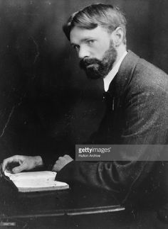 English author D H Lawrence (1885 - 1932) reading a book at his desk. Original Artwork: By Elliott & Fry.