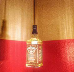 Garrafas de whisky geralmente tem um design refinado e que se destaca entre outras bebidas. Nesta foto, ela deu origem a um pendente. Você pode fazer em casa: com uma fiação adequada, lâmpada e soquete, é possível fazer a parte superior. A lâmpada pode entrar pelo interior, que pode ser cortado.