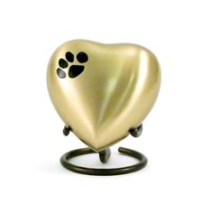 - Beautiful bronze pet cremation keepsakes are heart shaped and accented with a single paw print. - Add ash through the cap on the back of the heart keepsake. - Engraving available. - Complemented by