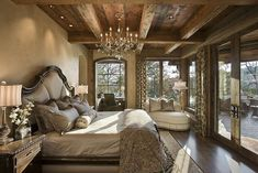A master bedroom with a view of the patio features dark hardwood floors; a tufted, oversized headboard; and niche office. Source: http://www.zillow.com/digs/Home-Stratosphere-boards/Luxury-Bedrooms/