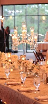 Some of the centerpieces will be crystal candelabras with clear hanging crystal prisms and votive cups surrounded by vintage bottles with single antique pink garden roses.