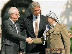 Israeli Prime Minister Yitzhak Rabin (left) and Palestine Liberation Organization Chairman Yasser Arafat (right) shake hands at the White House in front of President Bill Clinton in September 1993. The new play OSLO is a dramatization of events that led to a historic agreement.