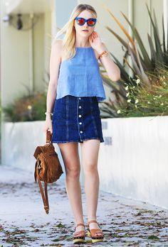 Dakota Fanning wears a button-front denim skirt with a denim top, brown sandals, a brown bag, and blue sunglasses