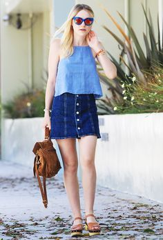 Dakota Fanning wears a button-front denim skirt with a denim top, brown sandals, a brown bag, and blue sunglasses