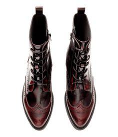 Weinrot. Stiefel aus Lederimitat mit Broguemuster. Modell mit spitzer Zehenpartie, Schnürung und seitlichem Reißverschluss. Futter aus Textil und Innensohle