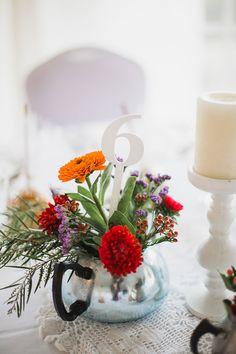 Bright whimsical vintage wedding reception teapot flower centrepieces