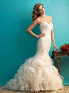 Gorgeous embroidered sheath, finished with a wealth of organza ruffles. Allure Bridal: 9254