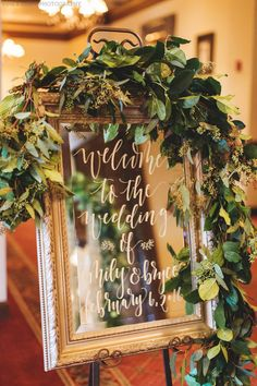 elegant wedding welcome sign features hand calligraphy in white ink on a gold framed mirror, dressed with a garland of seeded eucalyptus and lemon leaf greenery