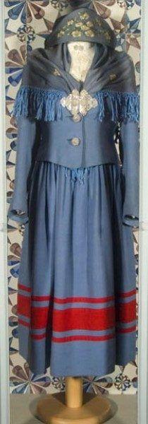 """Blaue Tracht. 1925-1950 Ärmelloses Faltenkleid, Falten (Breite ca. 3 cm) in Taille fixiert, Leibchen (von Schulter bis Taille) 23,5 cm lang. Brustausschnitt 9 cm lang, 13 cm breit. Leibchen schliesst vorne mit 3 Druckknöpfe. Auf Drückknöpfe """"Friesenknöpfe"""" genäht. Brustausschnitt rote Bordüre (Breite 3,3-4cm) aus Wollgewebe (Köperbindung). Bordüre mit nordischen Mustern in blauer Hochstickerei. 2 Bänder aus selben Stoff 3,5 cm vom Saum entfernt auf Rock genäht (Breite 2x2cm). #Sylt"""