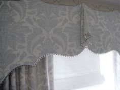 Lewis and Wood Venetian Damask on an elegantly shaped bucram pelmet with Sanderson trimming. Shaped upper line for added glamour ;-)