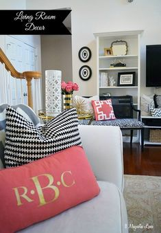 Black, white, coral, and gold decor give this eclectic living room lots of fun color.
