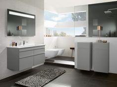 Une salle de bains baignée de lumière aux touches grises et blanches avec du carrelage assorti