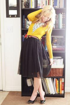 Striped shirt, yellow cardigan, black skirt, and black shoes.
