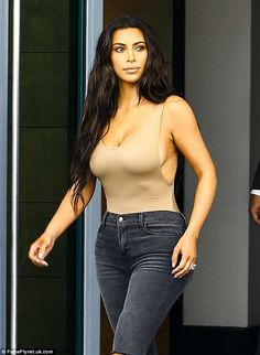 In the nude! Kim Kardashian shows off her curves as she goes braless in a skintone bodysuit on Friday in Miami