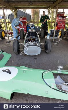 Download this stock image: 1962 Lotus-Climax 24 in the paddock with mechanics, 72nd Goodwood Members meeting, Sussex, UK. Clark-Stewart Cup racer. - DYTKF4 from Alamy's library of millions of high resolution stock photos, illustrations and vectors.