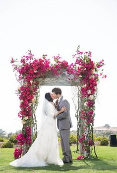 A romantic floral arbor covered in bright bougainvillea, fushia roses, and blush hydrangeas, created by Sunny Ravanbach of White Lilac Inc. | Brides.com: 30 Amazing Ceremony Structures