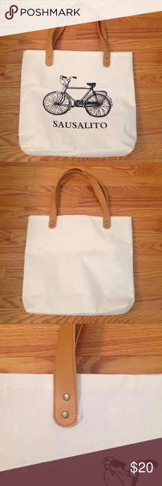 White Canvas Bicycle Saulsalito Tote Bag Cute canvas bicycle tote bag from Sausalito, CA. Plastic tag is still attached and it's never been used. Brand new condition. Size is about 14 x 14 inches. Perfect for taking shopping or to the beach. Bags Totes