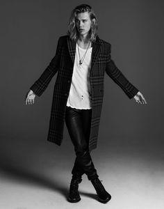 Austin Butler standing in long coat with his arms spread open