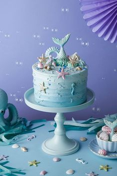 Mermaid CakeUnder the sea! This rippled mermaid buttercream cake is decorated with golden shells, pastel sea horses, pearlescent meringue kisses and topped with a blue mermaid tail.The cake shown on the image is a 6 inch.& cake will be supplied on a s Mermaid Birthday Cakes, Mermaid Cakes, Mermaid Tail Cake, Birthday Cake Girls, Birthday Ideas, Girls 1st Birthday Cake, Mermaid Party Food, Mermaid Parties, Cupcakes
