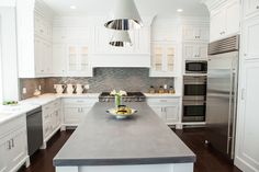 Stunning white and gray kitchen features white cabinets paired with white marble perimeter countertops and gray glass mosaic tiled backsplash.