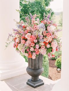 Lavish flower arrangements of garden roses, lilacs, peonies, ranunculus and hydrangeas scattered throughout the ceremony and reception areas.