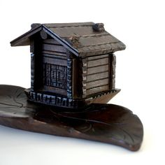 Vintage 1930s Black Forest, carved wooden inkwell and pen rest in the form of a wonderfully detailed leaf and chalet, the hinged roof of the cute, little chalet lifts up to reveal the glass inkwell. Approx measurements: Length 8 1/2 x W 4 3/4 x H 3 or L 21 1/2 cm x W 12 x H 7 1/2 cm  It is in good condition with a beautiful, slightly aged patina, there are signs of wear to the raised, roof details, most notably to the one to the near right, and some wear or damage to the b...