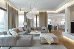 Clean modern living room with light taupe walls and curtains salon contemporain avec clairage indirect amnag avec des canaps gris clair et une table basse blanche aloadofball Gallery