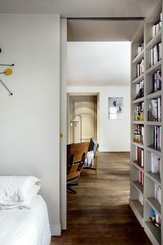 Small-space solution: A pocket door. This example is in a small Paris apartment remodeled—and lined with built-in bookshelves—by architect Philippe Harden