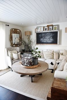 Neutral living room with a tasseled throw, rustic chalkboard and farmhouse-styled decor
