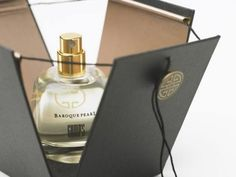 This fragrance packaging uses a black, four sided box with a string to lower…