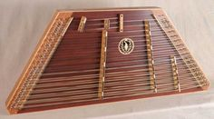 This James Jones 3/16/15/8 Travel Hammered Dulcimer has a Lacewood frame, a stained Redwood soundboard, Lacewood pin panels, Cherry bridges and Sycamore trim.