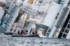 Rescuers arrive on a jet ski next to the Costa Concordia cruise ship that ran aground off the west coast of Italy, at Giglio island Jan. 15, 2012. Teams were painstakingly checking thousands of rooms on the cruise ship for people still missing. (Max Rossi/Reuters) #
