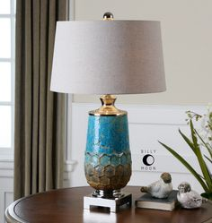 blue ceramic with rust brown accents and polished nickel plated details the slightly tapered round hardback shade is a light oatmeal linen fabric brown linen fabric lighting