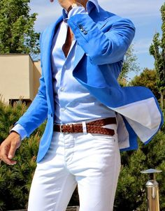 Bright blue jacket. Pale blue shirt. Brown woven belt. White trousers.