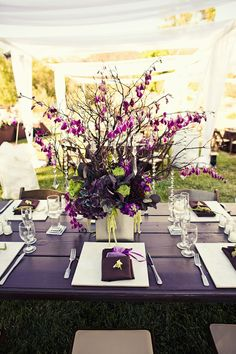Reception table centerpiece with purple, light green flowers with dangling crystal arrangements