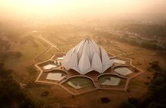 """Lotus Temple - Delhi, India  A holy place of worship for followers of the Bahá'í Faith, the Lotus Temple has won numerous architectural awards, making it one of the most recognisable buildings in India. Like all other Bahá'í places of worship, the temple is open to anyone of any religion. The """"petals"""" of the lotus flower are made of pure marble imported from Greece."""